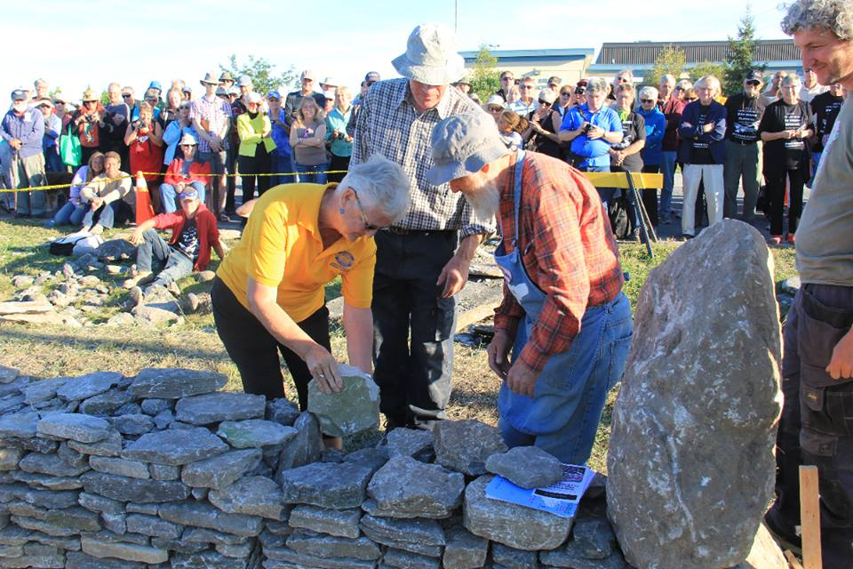 Joyce Haines Amherst Island Women's Institute President assisted by Norman Haddow laying a stone sent from the Women's Institute in Ards Ireland